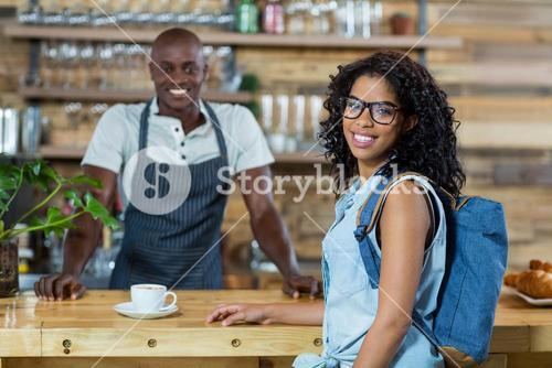 Portrait of woman and waiter smiling at counter