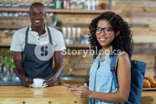 Woman using mobile phone while waiter standing in background