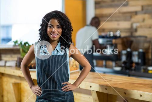 Portrait of smiling waitress standing with hands on hip at counter