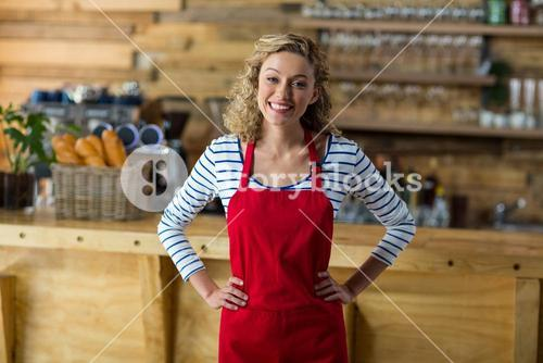Smiling waitress standing with hands on hip in cafe