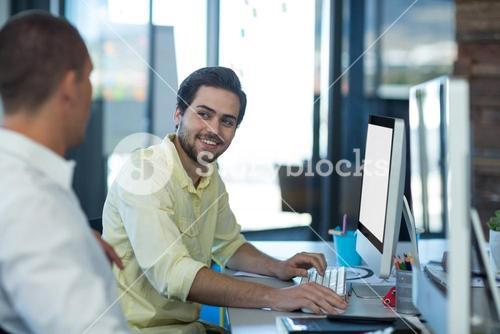 Businessmen interacting while working on personal computer