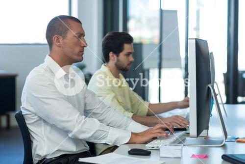 Attentive businessmen working on personal computer