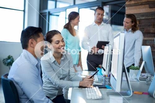 Businesspeople interacting while working on personal computer