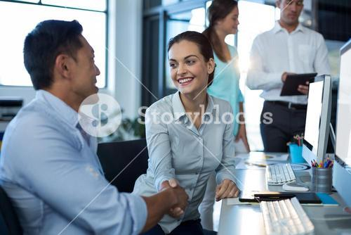 Businesspeople shaking hands at desk