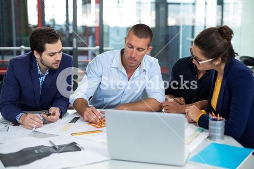 Businesspeople drawing diagram on chart
