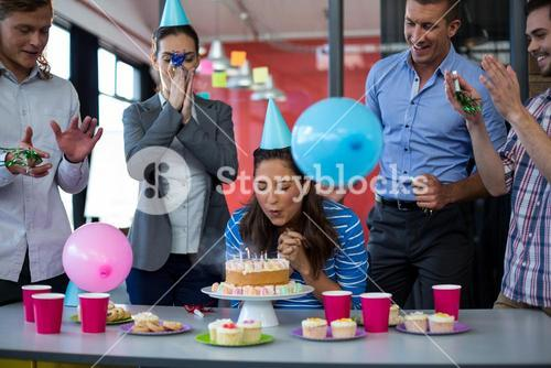 Businesspeople celebrating their colleagues birthday