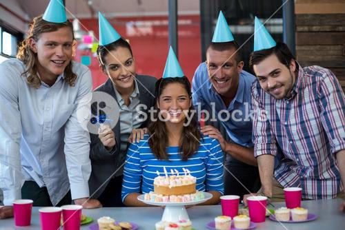 Portrait of businesspeople celebrating their colleagues birthday