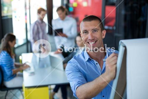 Portrait of businessman writing on flip chart
