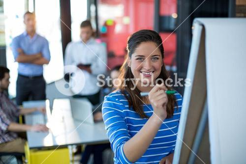 Portrait of businesswoman writing on flip chart