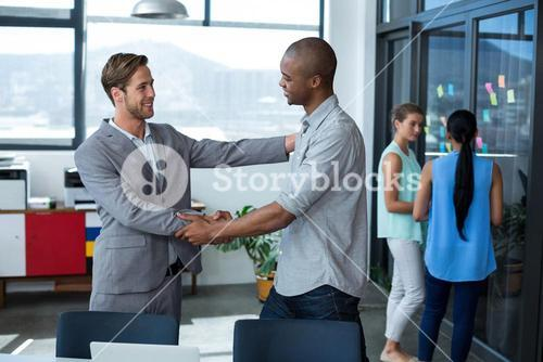 Business executives shaking hands in office
