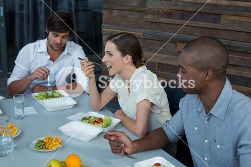 Business executives having meal on dining table