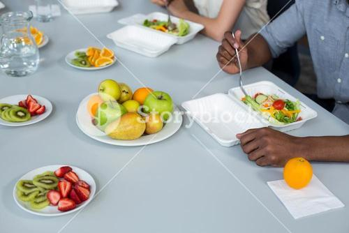 Business executives having meal on dining table in office