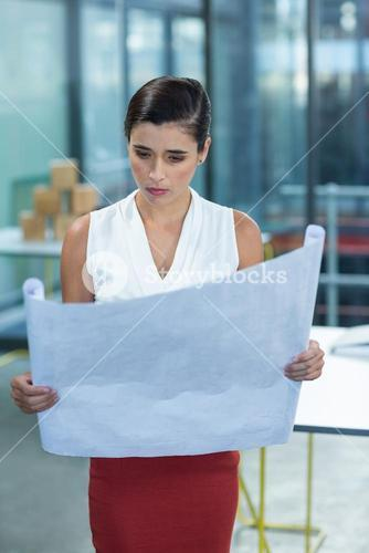 Female business executive looking at blueprint