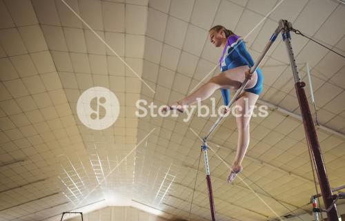 Female gymnast practicing gymnastics on the horizontal bar