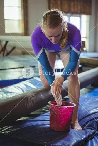 Female gymnast applying chalk powder on her hands before practicing