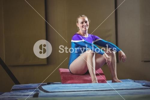 Female gymnast sitting on big wedge in the gymnasium