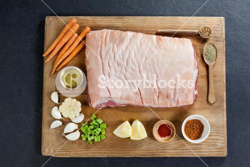 Beef brisket and ingredients on wooden board