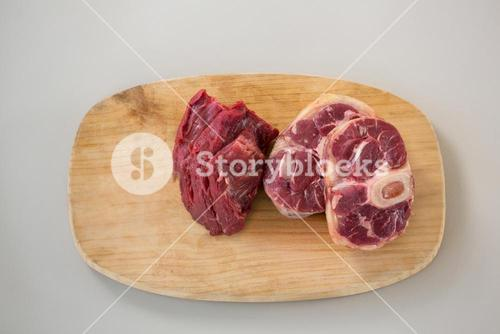 Sirloin chop and beef steak on wooden tray