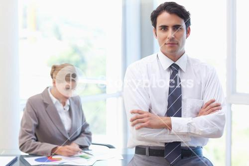 Businessman posing while his colleague is working