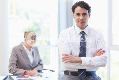 Young businessman posing while his colleague is working