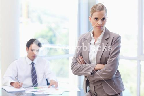 Serious businesswoman posing while her colleague is working
