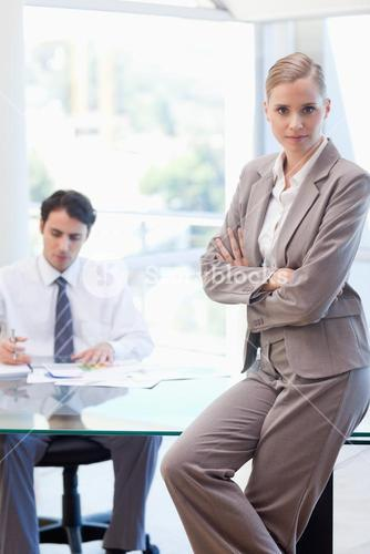 Portrait of a businesswoman posing while her colleague is working