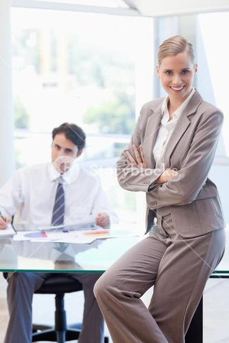 Portrait of a smiling businesswoman posing while her colleague is working