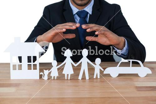 Mid section of businessman protecting paper cut out family, house and car with hands