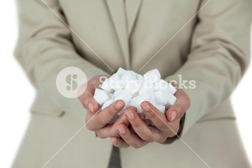 Womans hands cupped with sugar cubes