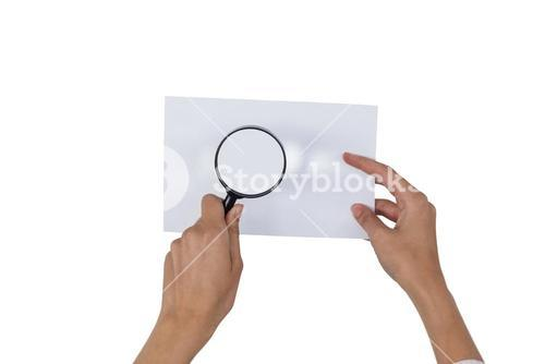 Close-up of woman holding magnifying glass on paper