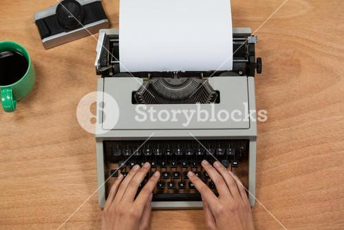 Businesswoman typing on typewriter with vintage camera, telephone and mobile phone