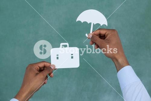 Man protecting paper cut out briefcase with umbrella