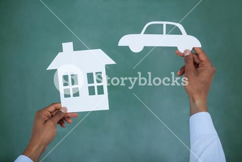 Man holding paper cut car and house