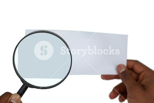 Close-up of man holding magnifying glass on paper