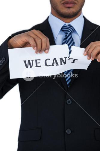 Conceptual image of businessman tearing a paper that reads we cant