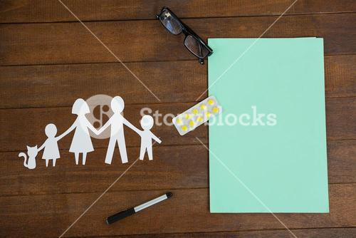 Paper cut out family chain with medicine and spectacles