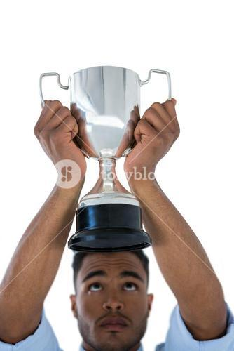 Close-up of businessman lifting a trophy
