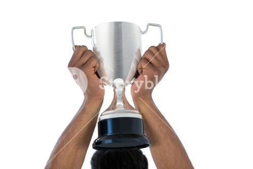 Hand of businessman lifting a trophy