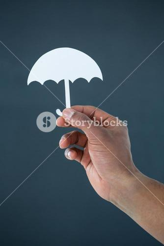 Hand of businessman holding paper cut out umbrella
