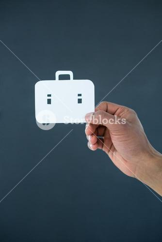 Hand of businessman holding paper cut out briefcase