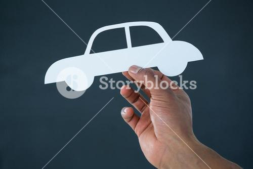 Hand of businessman holding paper cut out car