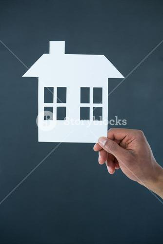 Hand of man holding paper cut out house
