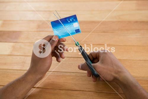 Businessman cutting credit card with scissors