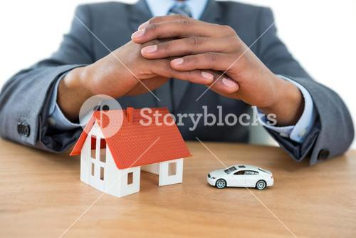 Businessman protecting house model and car with hands