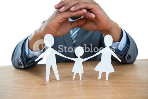 Businessman protecting paper cut out family with hands