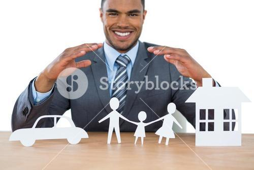 Smiling businessman protecting paper cut out family, house and car with hands