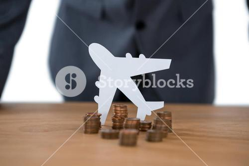 Stack of coins with paper cut out plane