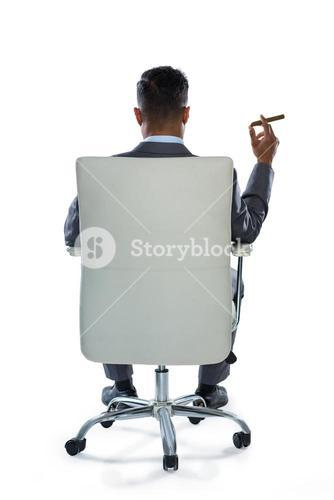 Rear view of businessman holding cigar