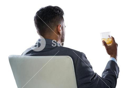 Businessman having glass of whisky against white background