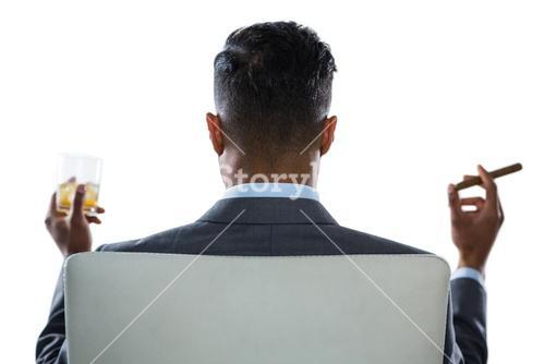 Businessman having glass of whisky and cigar against white background